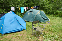 Folding camping chair and tent in meadow Stock Photos