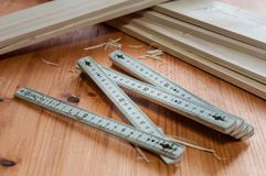 A folding carpenter`s ruler. On a wooden table Stock Photography