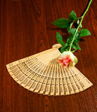 Folding carved sandalwood fan and pink-white rose Stock Images
