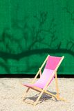Folding Chair in front of green wall Royalty Free Stock Photos