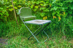 Folding chair. Metal folding chair on the grass Royalty Free Stock Photos