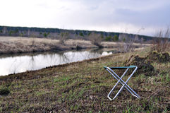 Chair. Folding chair near the river in a spring evening Royalty Free Stock Photos