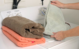 Folding clean towels and laundry Royalty Free Stock Photo