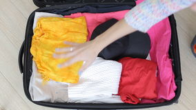 Folding clothes in travel bag.  stock video footage
