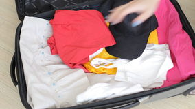 Folding clothes in travel bag.  stock footage