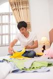 Folding clothes. Vietnamese young father folding clothes of his child Royalty Free Stock Image