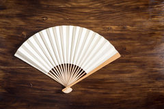 Folding fan. Blank traditional folding fan on space of old wood Royalty Free Stock Photos
