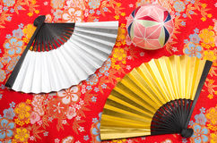 Folding fan and handball. Folding fan and traditional japanese handball on the patterned old japanese cloth Stock Photo