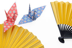 Folding fan and origami bird. Golden folding fan and origami bird isolated on white background Stock Image