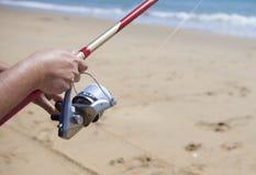 Folding the fishing line on the beach. Folding the fishing line. Sea angling sport at the beach stock image