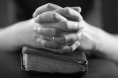 Folding Hands. Woman folding hands over her bible and praying to God stock image