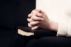 Folding hands and pray. Woman folding hands over her holy bible and praying to God Royalty Free Stock Photo