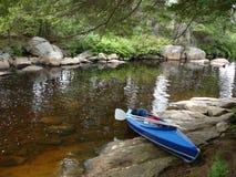 Folding kayak by shore. Folding kayak with paddles by lake's shore. Adirondack State Park, NY stock photos