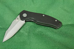 Folding knife on a green background Stock Photos