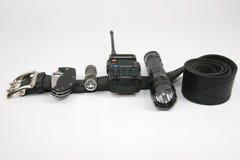 Folding knife, radio transmitter a flashlight and a Taser on a b Stock Photo