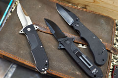 Folding knives on leather retro bag tablet in rarity store Royalty Free Stock Image