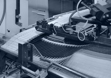 Folding machine detail. Blue toned detail of a folding machine royalty free stock images