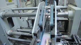 Folding machine folds printed offset sheet as part of newspaper brochure in print house stock footage