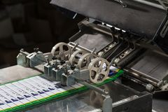 Folding machine industrial. Demonstration of the workflow. Equipment for color printing. stock image