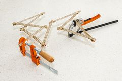 Folding meter stick and two adjustable clamps as an abstract conceptual installation art Royalty Free Stock Photos