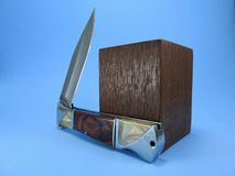 A folding pocket knife next to a wooden block on a blue background royalty free stock images
