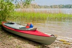 Folding red canoe on Lake Stock Image