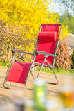 Folding red chair on backyard patio Stock Photos