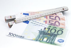 Folding rule with money. Image shows banknotes which are clamped in a folding ruler royalty free stock image