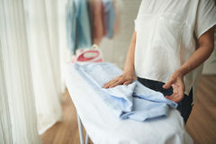 Folding shirt. Close-up image of woman folding clothes after ironing Royalty Free Stock Photos