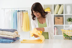 Folding shirt. Mature pretty housewife folding freshly washed shirts Stock Photos
