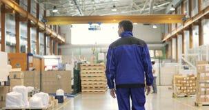 Folgen Sie Gesamtlänge des Arbeiters, der durch industrielle Anlagen geht stock video