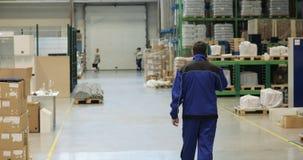 Folgen Sie Gesamtlänge des Arbeiters, der durch industrielle Anlagen geht und am Handy spricht stock footage