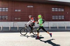 folgender Radfahrer der laufenden Straße des Frauenläufers reitet im Mai Sturm Lauf stockfoto