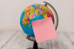 Folha cor-de-rosa lisa sticked ao globo artificial acima da tabela de madeira Papel de nota vazio unido na frente do mini mundo fotografia de stock royalty free