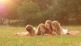 Folha da criança através de um livro no jardim no gramado um o dia de verão video estoque