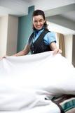 Folha de cama de arranjo assistente fêmea entusiástica Imagem de Stock Royalty Free