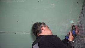 Folha de fixação da placa de gesso do indivíduo mestre da construção ao teto com broca closeup filme