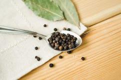 Folha de louro das ervilhas da pimenta preta uma tabela de madeira do guardanapo da colher Foto de Stock