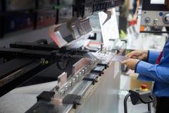 Folha de metal de dobra do operador pela máquina de dobra da folha Imagem de Stock Royalty Free