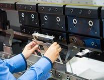 Folha de metal de dobra do operador pela máquina de dobra da folha Fotografia de Stock Royalty Free