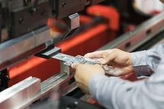 Folha de metal de dobra do operador pela máquina de dobra da folha Fotografia de Stock