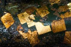 Folha de ouro dourada na superfície oleosa escura Imagens de Stock Royalty Free
