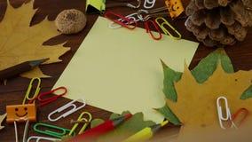 Folha de papel amarela com as folhas de bordo e materiais de escritório caídos amarelos video estoque