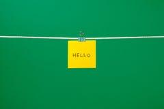 Folha de papel amarela na corda com texto olá! Fotografia de Stock Royalty Free