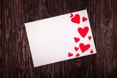 Folha de papel branca o fundo de madeira dos corações vermelhos pequenos Imagens de Stock