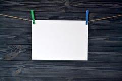 A folha de papel branca prendeu com um pregador de roupa em uma parede de madeira fotos de stock