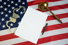 Folha de papel branca pura em um fundo de América da bandeira com um martelo de um juiz e de algemas fotografia de stock royalty free
