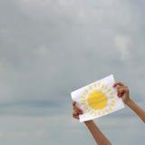 Folha de papel com imagem do sol contra o céu nublado Imagens de Stock Royalty Free