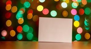 Folha de papel com lugar para seu conceito de projeto do texto em um bokeh da luz de Natal da tabela Fotografia de Stock Royalty Free