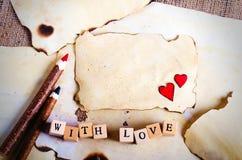 Folha de papel do vintage velha, dois corações vermelhos, lápis de madeira e palavras com amor em cubos na serapilheira, fundo do Imagens de Stock